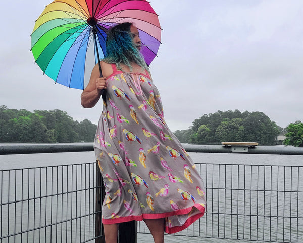 Woman standing outside by a river with a colorful bird print dress and a rainbow umbrella.