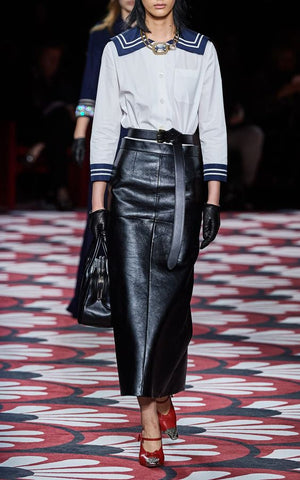Woman on catwalk wearing a leather skirt and white middy top with blue trim