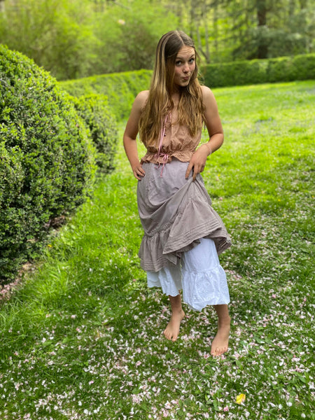 Young woman raising her purple petticoat to show off drawers on a spring day.