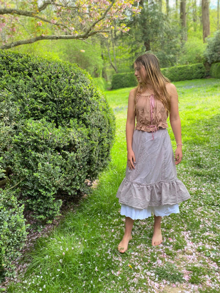 Young woman outside by a boxwood hedge wearing a purple petticoat and pink cami.  It is springtime.