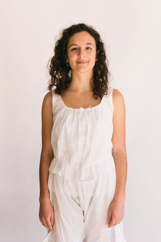 Woman wearing a white camisole.