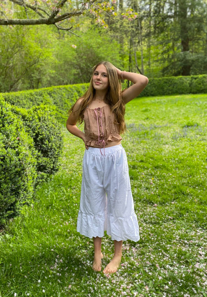 Young woman standing by a boxwood hedge wearing white drawers and a pink camisole.