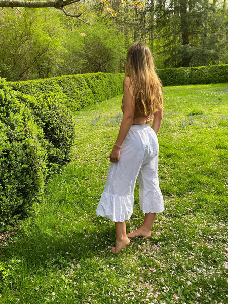 Young woman standing by a boxwood hedge wearing white drawers and a pink camisole. Her back is turned.