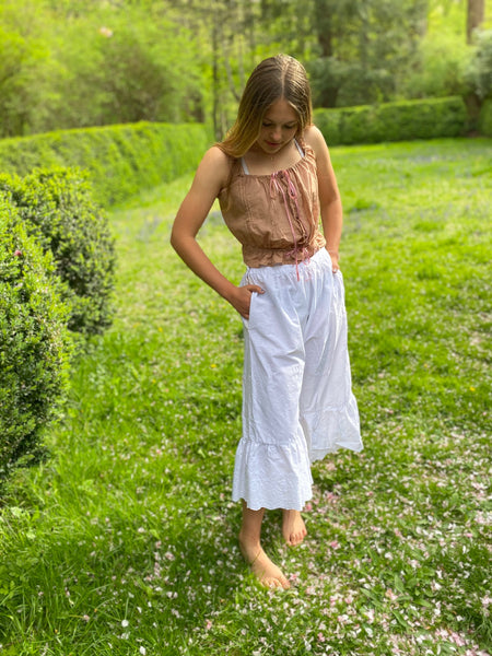 Young woman standing by a boxwood hedge wearing white drawers and a pink camisole.  Her hands are in the plackets