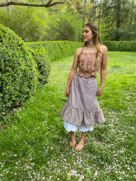 Young woman beside boxwood bushes outside wearing a pink camisole, lilac petticoat, and white drawers.
