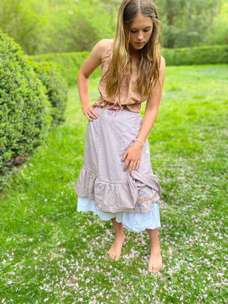 Young woman wearing a purple petticoat, pink cami, standing by boxwood hedge.
