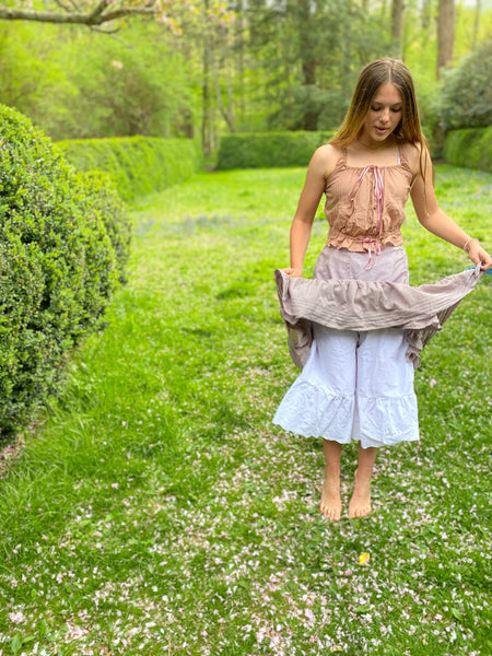 Young woman by a boxwood hedge lifting her petticoat to show drawers underneath
