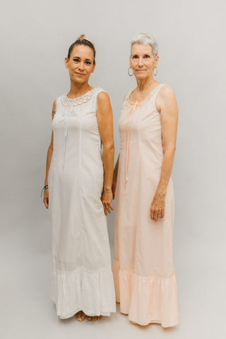 Two women wearing floor length white and pink nightgowns.