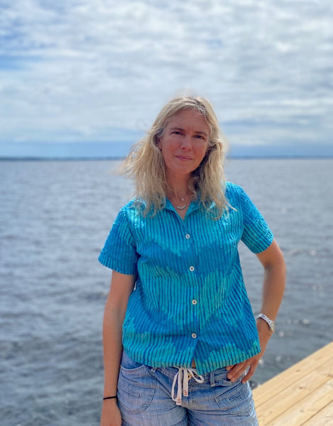 Woman standing by a river wearing a teal block printed button down shirt.