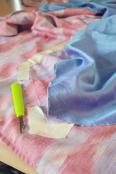 Adjusting the 261 Paris Promenade Dress of pink fabric with blue overlay with a seam ripper and tape.