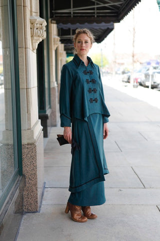 White woman outside wearing a dark teal 1910s suit with black trim