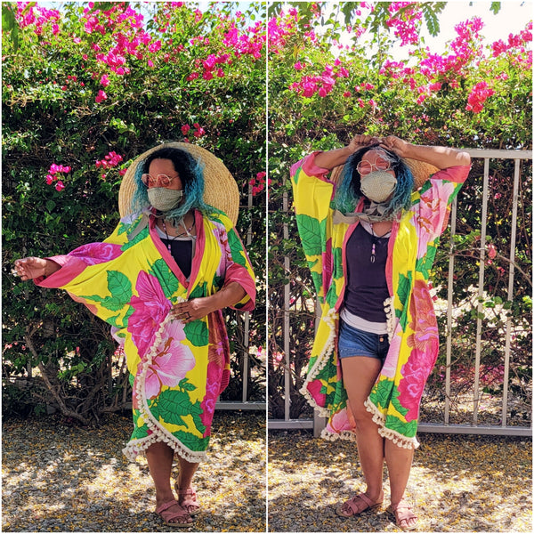 Woman wearing Poirot Cocoon Coat made of a bright yellow and pink African Wax Print.