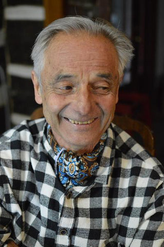 Older man wearing a silk paisley cravat and a black and white buffalo check shirt.