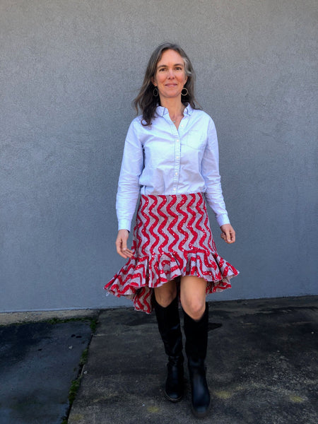 Woman walking toward camera wearing a red skirt with flounces and a blue button down shirt