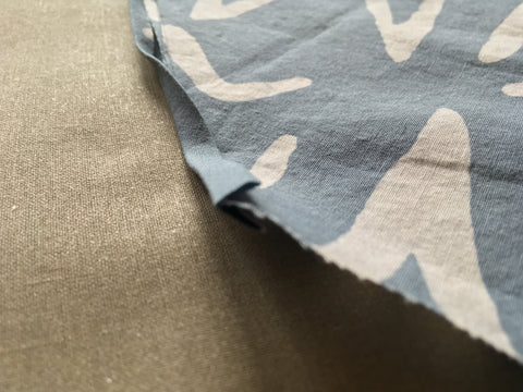 Photo up close of raw egde of fabric sandwiched in fold of bias tape