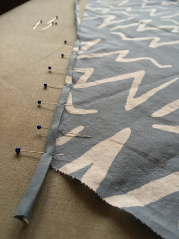 Phot of bias tape and fabric pinned together at raw edge