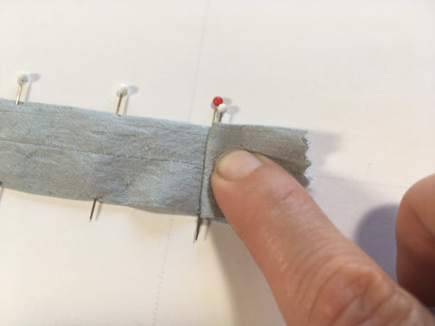 The first box-pleat fold matching white pin to red pin.