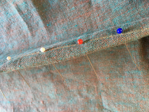 The pins aligned in the dart guidelines creating the foldline