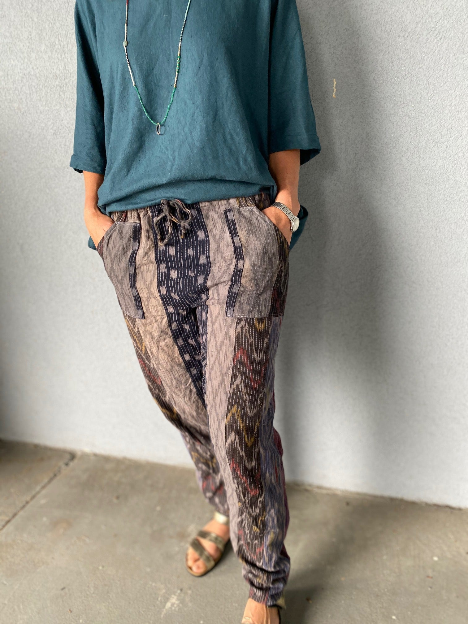 Bottom half of woman wearing ikat pants, hands in pockets, teal top.