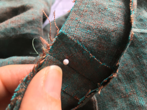 Using a pin to align armhole facing to shoulder seam