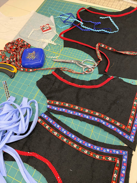 layout of black fabric pieces for 126 Vests of Greece and Poland, short Greek vest, with trim of embroidered ribbon, bias tape, and braid.