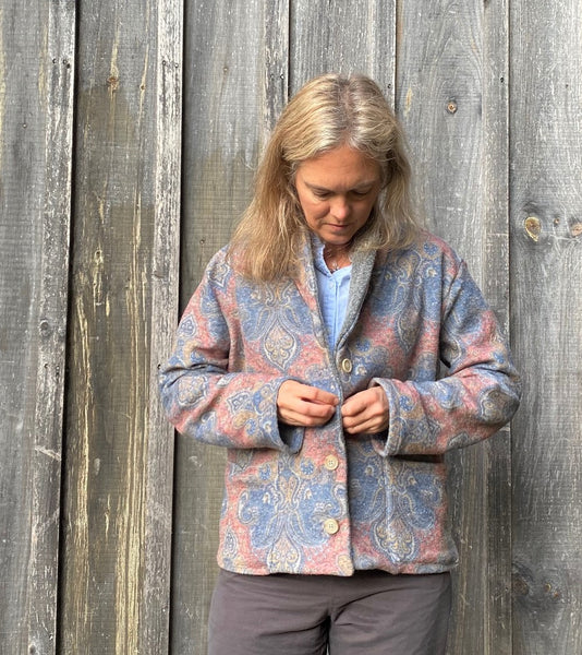Woman standing in front of a wooden wall wearing a wool printed jacket.