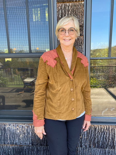 Woman standing in front of windows wearing a brown jacket with rust colored trim.
