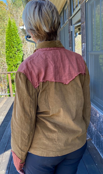 back of woman's jacket standing outside in front of a house.