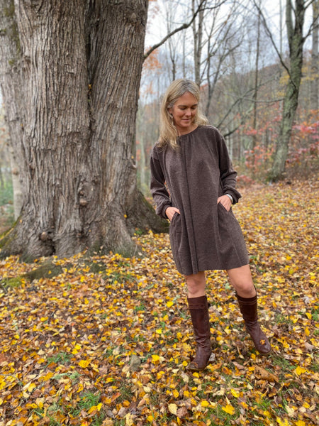 Woman wearing a short brown dress with brown boots standing outside under a tree with yellow leaves on the ground.