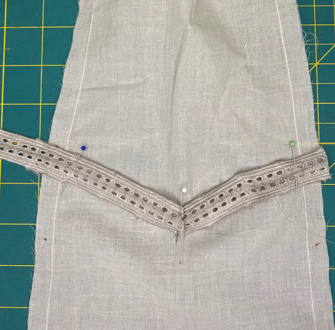 grey insertion lace pinned to fabric.