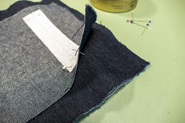 Using pins to align the corner dots on the Garment fabric and the pocket welt.
