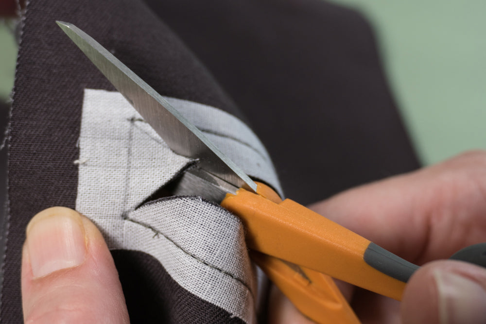Cutting to corner of welt pocket opening.