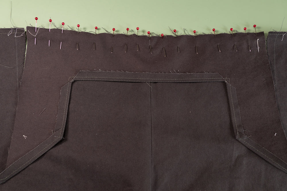 The Front Buttonhole Facing pinned to the front of the pant.