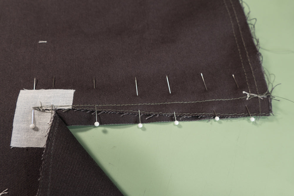 The Front Buttonhole Facing is stitched to the front of the pant on one side over the the stitch line guide.