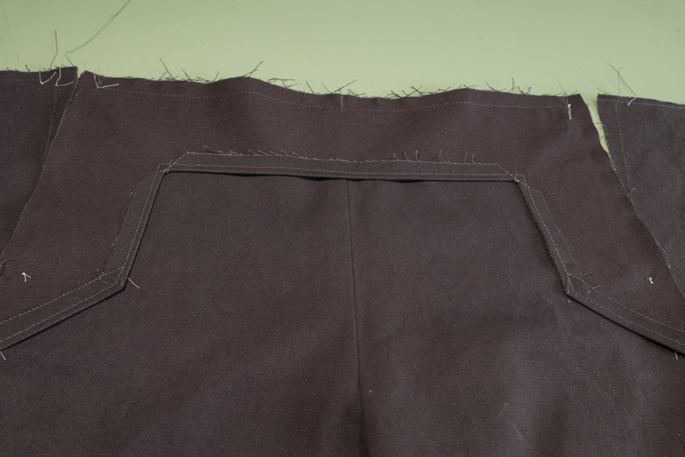 The top of the Front Buttonhole facing sewn to the top of the pant.