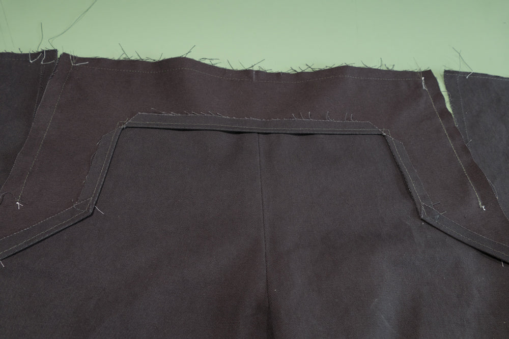 the top and both sides of the Buttonhole Facing sewn to the pant front.