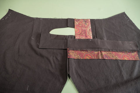 Pocket bag sewn to top of pant and on the bottom edge of the waistband.