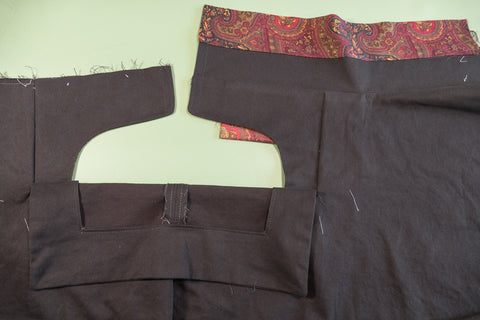 View of the front of the pant with the waistband attached  and the coin pocket peeking out.