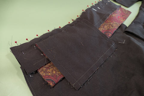 Waistband with welt pocket pinned to the pants and ready to be sewn.