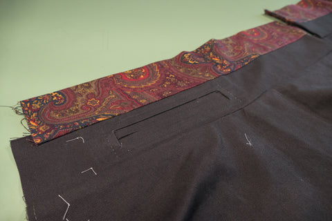 The left waistband with the welt pocket and the waistband curtain laying open.