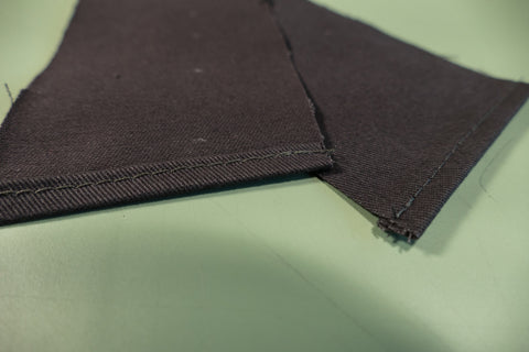 The top edges of both Center Back Eyelet Facing turned under and stitched close to the fold edge to finish.