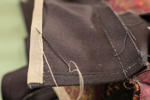 Whip stitching the seam binding to cover the raw edge.