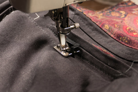 Using a blind hem foot to topstitch at the welt pocket.