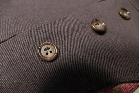 Only half of the button is sewn onto the pants until alignment is perfect.