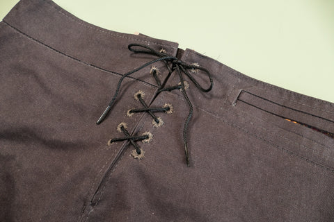 Thread a string or lace through the eyelets and tie at the top.