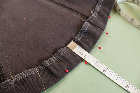 Measuring a one inch hem on the curved godet edge.