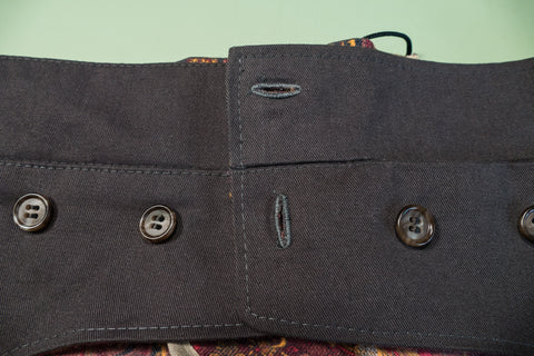 The buttonhole on the waistband is horizontal the buttonhole on the front dart gusset is vertical.