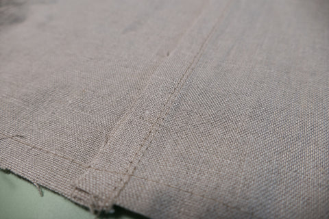The wrong side of the sleeve edge stitched with the seam pressed to the back.