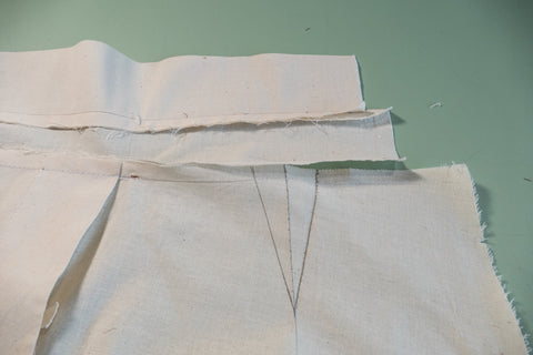 With wrong side facing up, the dart drawn at the pant waist.