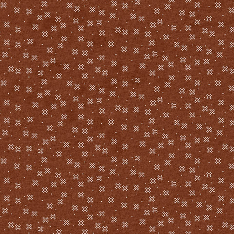 Rust colored fabric with a small white repeating cross pattern